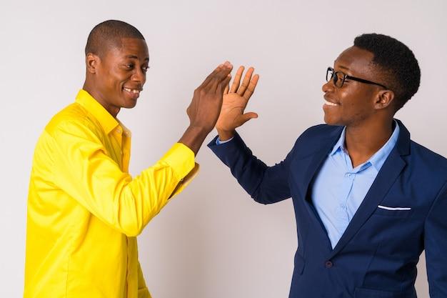 Studioaufnahme des jungen kahlen afrikanischen geschäftsmannes und des jungen afrikanischen geschäftsmannes zusammen gegen weißen hintergrund