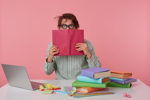 Studioaufnahme des jungen mannes kerl mit brille, trägt auf leerem hemd, sitzt an einem tisch mit büchern, arbeitet an einem laptop, guckt überrascht auf das buch, das sein gesicht bedeckt, isoliert über rosa hintergrund.