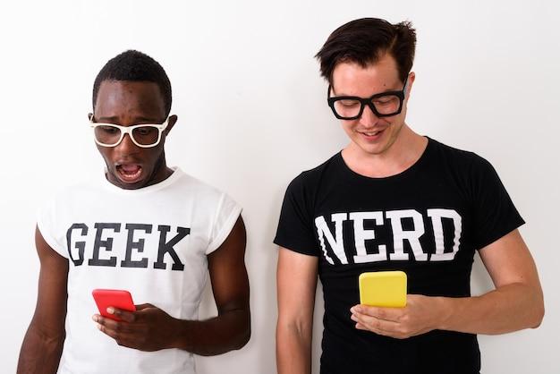 Studioaufnahme des jungen schockierten schwarzafrikaner-geek-mannes mit handy