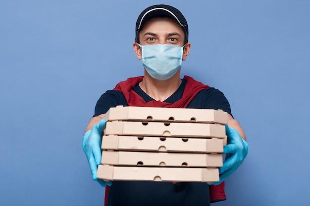 Studioaufnahme des kuriers, der stapel von pizzaschachteln hält, lieferbote, der dem kunden befehl erteilt, kellner liefert essen vom online-restaurant, kerl, der schutzmaske und handschuhe trägt