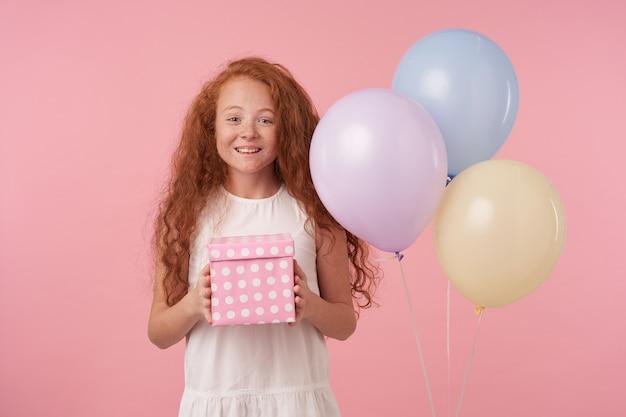 Studioaufnahme des lockigen weiblichen kindes mit dem langen foxy haar, das geschenkverpackungsbox hält, aufgeregt und überrascht ist, geburtstagsgeschenk zu erhalten, glücklich in der kamera über rosa hintergrund schauend