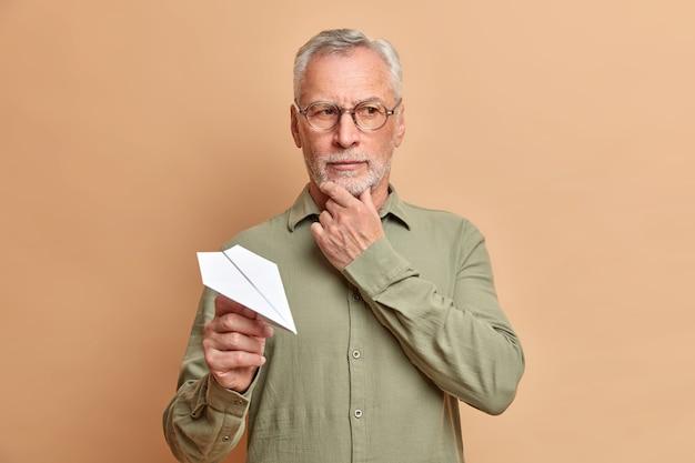Studioaufnahme des nachdenklichen europäischen mannes hält kinn und schaut nachdenklich weg denkt tief über etwas nach, das gute idee hält hält papierflugzeug trägt brille und hemd isoliert auf brauner wand