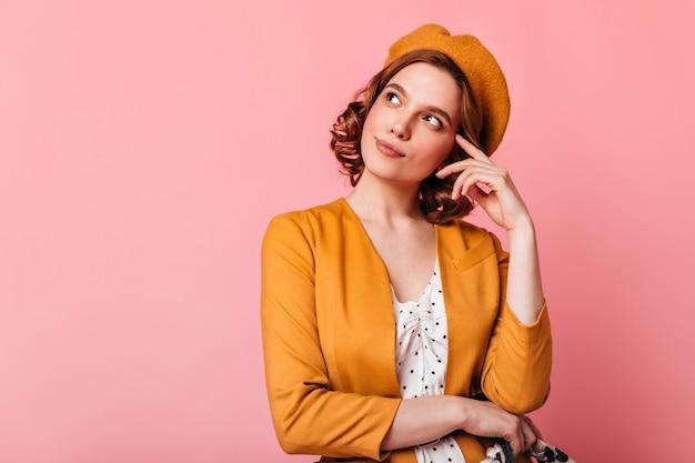 Studioaufnahme des nachdenklichen französischen mädchens, das oben schaut. charmante junge frau in baskenmütze, die an etwas auf rosa hintergrund denkt.