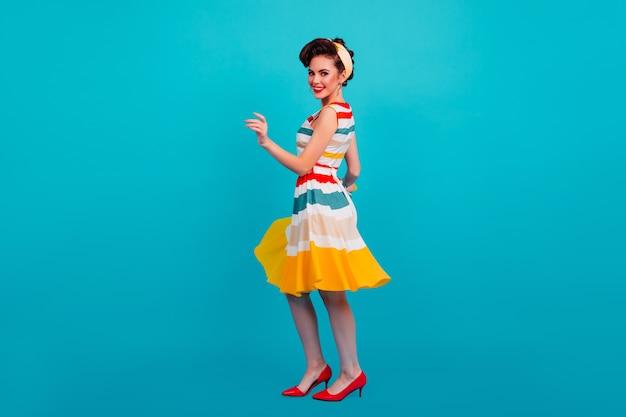 Studioaufnahme des pinup-mädchens, das gestreiftes kleid trägt. ansicht der tanzenden stilvollen frau in voller länge.