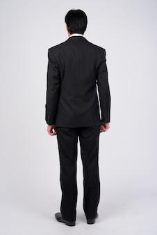 Studioaufnahme des reifen gutaussehenden geschäftsmannes, der smoking gegen weiß trägt