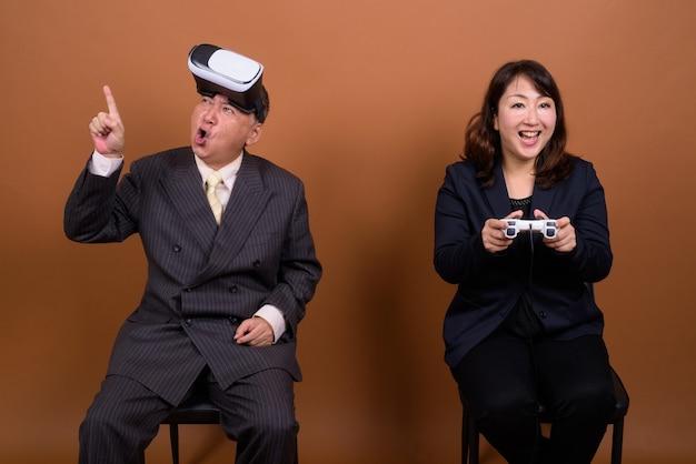 Studioaufnahme des reifen japanischen geschäftsmannes und der reifen japanischen geschäftsfrau zusammen vor braunem hintergrund