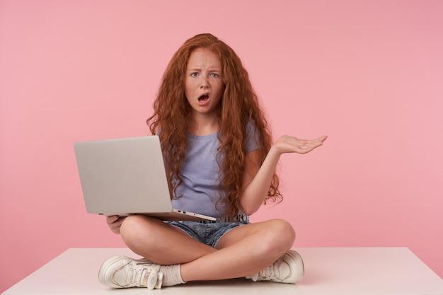 Studioaufnahme des rothaarigen lockigen mädchens mit langen haaren, die kamera mit verwirrtem gesicht betrachten und laptop auf beinen halten, palme mit schmollmund anhebend, über rosa hintergrund in blauem t-shirt und jeansshorts posierend