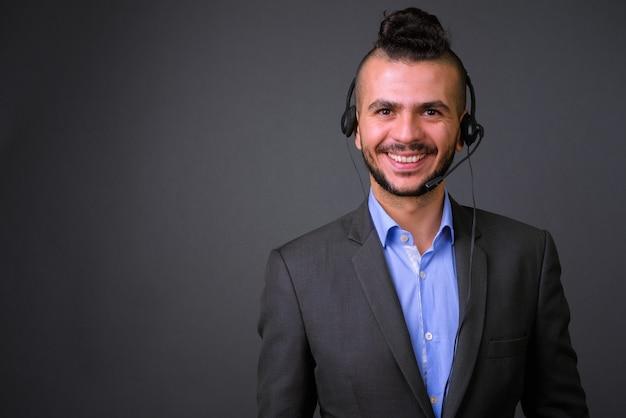 Studioaufnahme des schönen türkischen geschäftsmannes, der headset trägt, das als call-center-vertreter gegen grauen hintergrund arbeitet