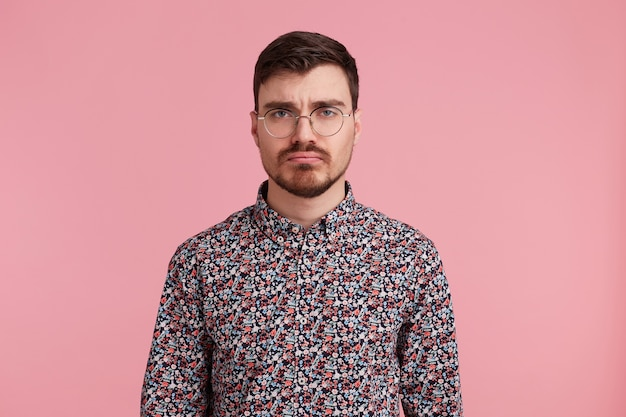 Studioaufnahme des traurigen jungen bärtigen mannes in den gläsern, die in einem bunten hemd tragen, lokalisiert über rosa hintergrund. menschen- und emotionskonzept.