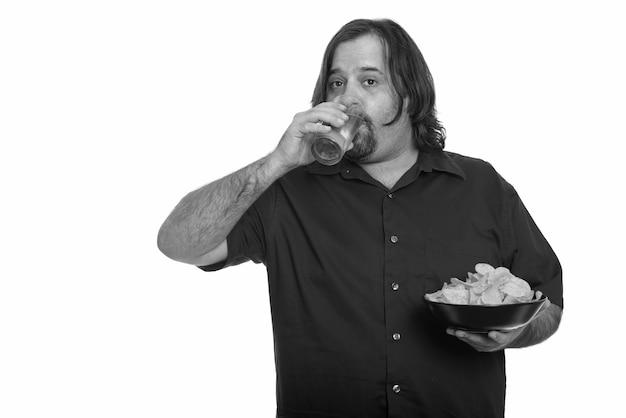 Studioaufnahme des übergewichtigen bärtigen mannes lokalisiert gegen weißen hintergrund in schwarzweiss