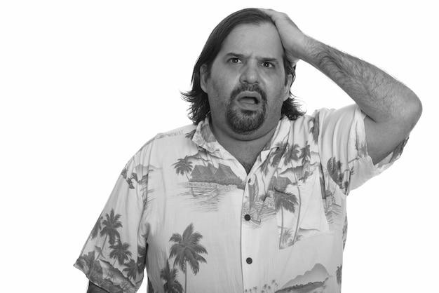 Studioaufnahme des übergewichtigen bärtigen touristenmanns bereit für urlaub lokalisiert gegen weißen hintergrund in schwarzweiss