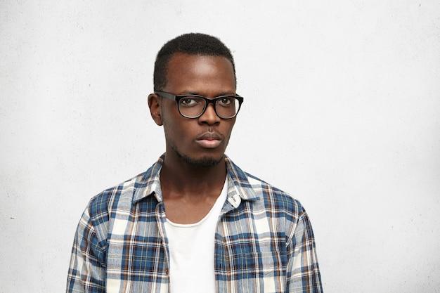 Studioaufnahme des verdächtigen jungen afroamerikanischen hipsters, der die stilvolle brille mit gerunzelter stirn trägt