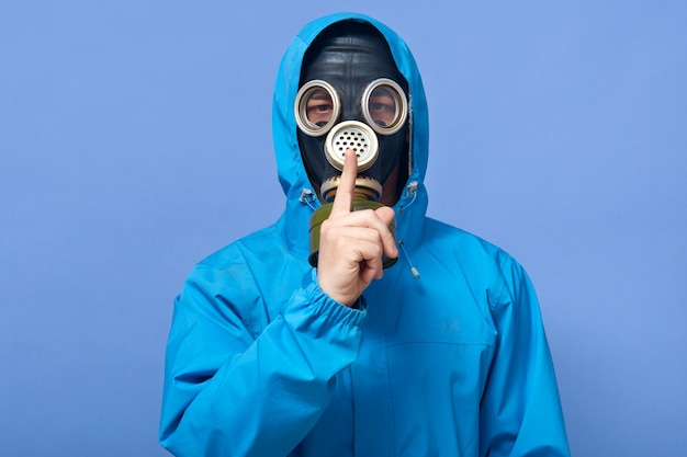 Studioaufnahme des wissenschaftlers, der uniform und gasmaske trägt, isoliert über blau aufwirft