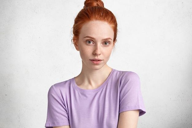 Studioaufnahme einer angenehm aussehenden ingwerfrau mit selbstbewusstem aussehen, lässig gekleidet, mit reiner sommersprossiger haut, attraktivem aussehen.