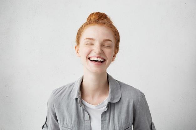 Studioaufnahme einer attraktiven fröhlichen jungen europäischen frau mit ingwerhaar und sommersprossen auf ihrem ganzen gesicht