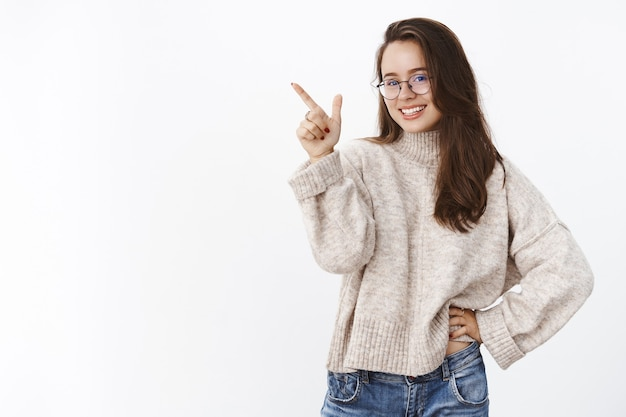 Studioaufnahme einer charmanten, intelligenten und selbstbewussten frau, die die wahl trifft und auf die obere linke ecke zeigt, um das produkt anzuzeigen, das vorne breit lächelt und weiß, dass sie über graue wand erfreut stehen möchte.
