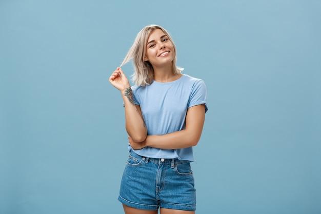 Studioaufnahme einer entspannten und entspannten beliebten attraktiven frau mit blonden haaren und tätowierungen