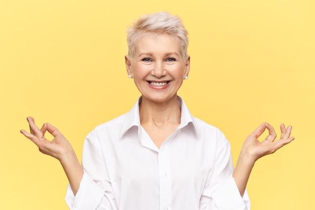 Studioaufnahme einer erfolgreichen reifen geschäftsfrau, die ein weißes formelles hemd trägt, das breit lächelt, mudra-geste macht, in ihrem büro meditiert, voller energie ist und vor gelbem hintergrund posiert