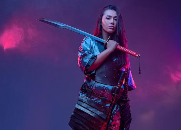 Studioaufnahme einer frau in samurai-outfit mit katana vor neonfarbenem hintergrund.