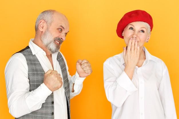 Studioaufnahme einer frivolen sorglosen frau mittleren alters in roter baskenmütze, die den mund nach luft schnappend bedeckt, wütender bärtiger kerl, der die fäuste ballt, einen wütenden blick hat und seine frau schlagen wird. häusliche gewalt