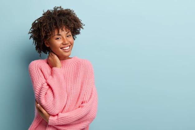 Studioaufnahme einer fröhlichen charmanten jungen frau mit afro-haarschnitt