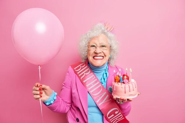 Studioaufnahme einer glücklichen, faltigen rentnerin mit hellem make-up, die zahnig lächelt, hält festlichen kuchen mit brennenden kerzen hat festliche stimmung trägt aufgeblasenen ballon