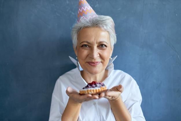 Studioaufnahme einer glücklichen schönen frau mittleren alters, die einen konischen hut trägt, der geburtstag feiert, isoliert mit kuchen in ihren händen aufwirft und ihnen anbietet, biss zu haben. selektiver fokus auf das gesicht der frau