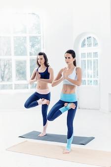 Studioaufnahme einer jungen frau, die yogaübungen auf weiß macht