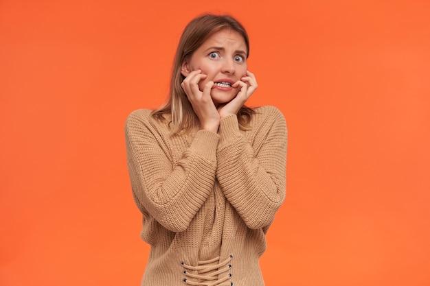 Studioaufnahme einer jungen kurzhaarigen blonden dame, gekleidet in einen beigen strickpullover, der erhobene hände auf ihren wangen hält, während sie ängstlich nach vorne schaut, isoliert über orange wand