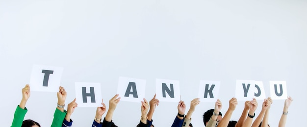 Studioaufnahme einer nicht erkennbaren, nicht identifizierten gruppe von stabsoffizieren in der unternehmenszentrale, die ein dankeschön-papppapierschild über dem kopf hält, das dem kunden auf weißem hintergrund wertschätzung zeigt.