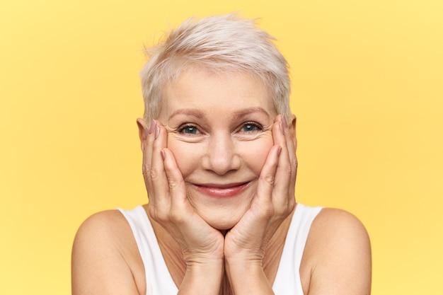 Studioaufnahme einer niedlichen lustigen frau mittleren alters mit gefärbten kurzen haaren lächelnd, wangen auf hände platzierend, kamera mit glücklichem neugierigem gesichtsausdruck betrachtend, etwas sehr interessantes sehend