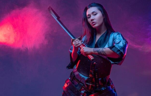 Studioaufnahme einer orientalischen kriegerin im cyberpunk-stil mit samurai-schwert.