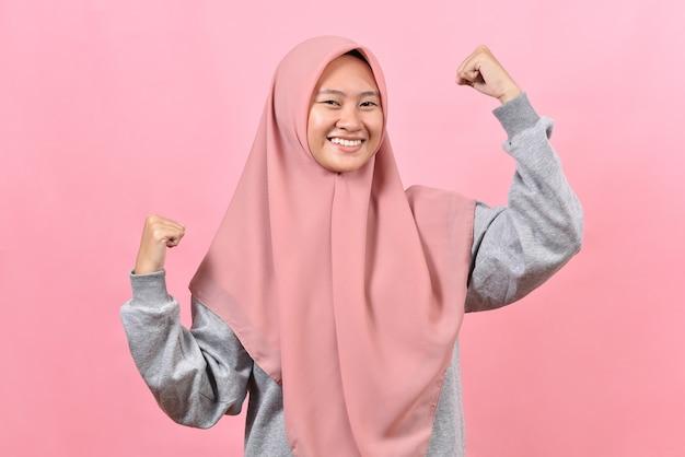 Studioaufnahme einer positiven jungen asiatischen muslimischen frau, die die arme hebt, zeigt, dass muskeln vorgeben, sehr stark zu sein und ein kraftvolles lächeln trägt sanft hijab einzeln auf rosafarbenem hintergrund.