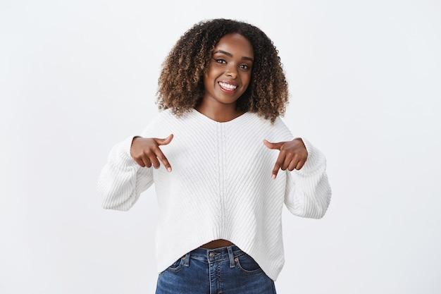 Studioaufnahme einer stylischen afroamerikanischen, fröhlichen mitarbeiterin im pullover, die nach unten zeigt und eine tolle werbung zeigt, die den blick empfiehlt und die werbung auscheckt, die glücklich über die weiße wand lächelt