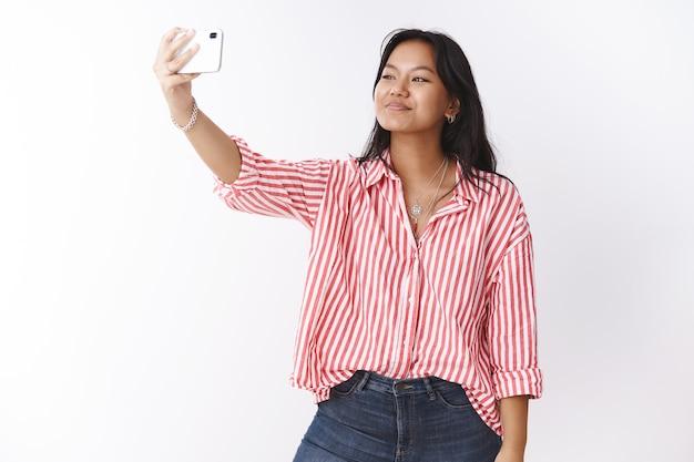 Studioaufnahme einer stylischen jungen, süßen asiatischen frau, die selfie macht, um follower im internet mit neuer trendiger bluse zu beeindrucken, die die hand mit dem smartphone ausstreckt, das auf den handy-bildschirm schaut und fotografiert