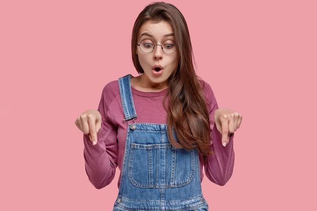 Studioaufnahme einer überraschten kaukasischen dame zeigt mit beiden zeigefingern auf den boden, ist erstaunt und fassungslos, enttäuscht von etwas