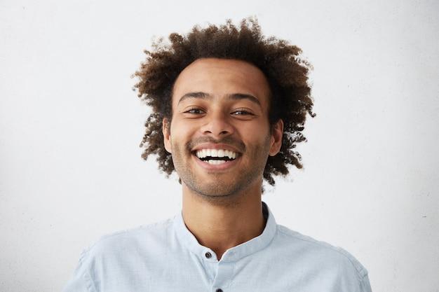 Studioaufnahme eines attraktiven jungen studenten, der über guten witz lacht