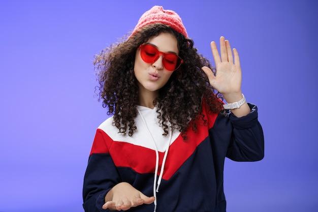 Studioaufnahme eines coolen und stylischen dj-mädchens in roter mütze und sonnenbrille, die die handfläche hebt, während sie coole musik genießt und zu rhythmischen lippen tanzt, die spaß auf einer fantastischen party haben, die über blauer wand chillt.