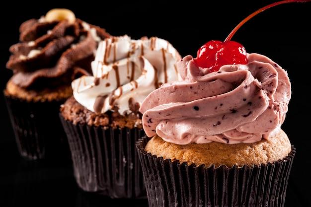 Studioaufnahme eines cupcakes auf schwarzem hintergrund.