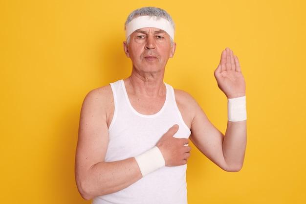 Studioaufnahme eines ernsthaften konzentrierten reifen mannes, der gegen gelbe wand aufwirft und weißes ärmelloses t-shirt und stirnband trägt