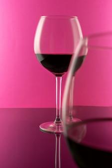 Studioaufnahme eines glases rotwein lokalisiert auf rosa hintergrundnahaufnahme. sauber und minimal. rotwein in einem großen glas. weinkonzept.