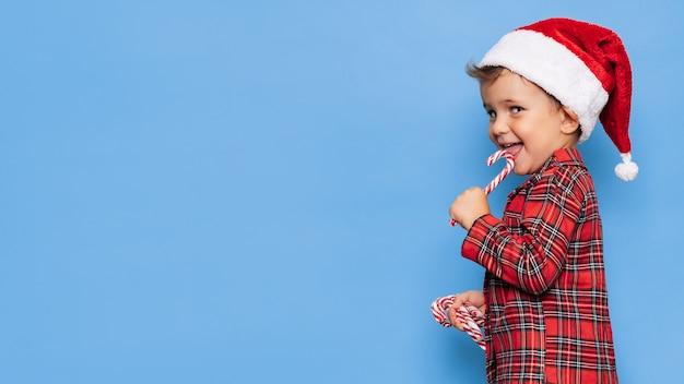 Studioaufnahme eines glücklichen jungen im weihnachtspyjama mit einem karamellstock in den händen. ein platz für ihren text. das konzept der ferien.