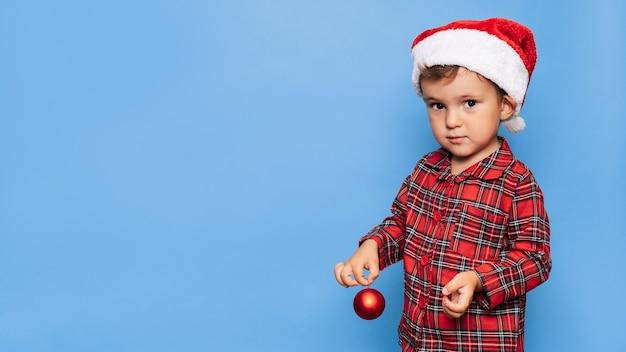 Studioaufnahme eines kleinen jungen im weihnachtspyjama. ein platz für ihren text. das konzept der ferien.