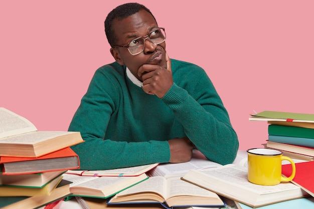 Studioaufnahme eines nachdenklichen schwarzen männlichen college-studenten, der beiseite konzentriert ist, über kreative lösung nachdenkt, lässigen grünen pullover trägt