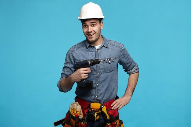 Studioaufnahme eines positiv freundlichen jungen konstrukteurs, der bohrer und gürtel mit allen instrumenten trägt, die für kunden renovieren