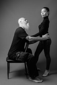 Studioaufnahme eines reifen, bärtigen, glatzköpfigen mannes und einer jungen schönen asiatin zusammen gegen graue wand in schwarz und weiß