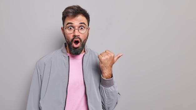 Studioaufnahme eines schockierten bärtigen erwachsenen mannes zeigt mit fassungslosem ausdruck beiseite