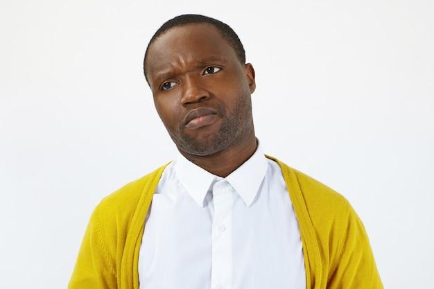 Studioaufnahme eines unzufriedenen unzufriedenen jungen afroamerikanischen mannes in gelber strickjacke und weißem hemd, der die stirn runzelt und sich beleidigt und enttäuscht fühlt. menschliche emotionen, gefühle und reaktionen