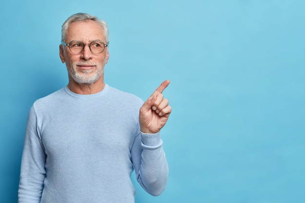 Studioaufnahme eines zufriedenen bärtigen alten europäischen mannes mit grauem haar gibt empfehlung, diesen kopienraum für ihre werbung zu verwenden, gekleidet in lässigem pullover isoliert auf blauer wand