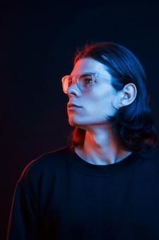 Studioaufnahme im dunklen studio mit neonlicht. porträt eines ernsten mannes